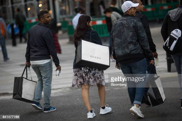Shoppers carry Gucci Ltd luxury goods shopping bags as they walk along New Bond Street in central London UK on Thursday Aug 31 2017 UK consumer...