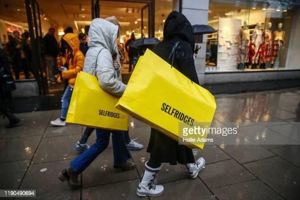 Shoppers carry large Selfridges bags during the Oxford Street Boxing Day Sales on December 26, 2019 in London, England.