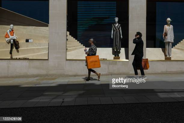 Shoppers carry Louis Vuitton bags past a Louis Vuitton luxury fashion store, operated by LVMH Moet Hennessy Louis Vuitton SE, in central London,...