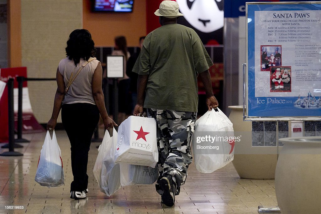 Shoppers carry Macy's Inc. bags while walking through the Fair Oaks Mall in Fairfax, Virginia, U.S., on Monday, Nov. 12. 2012. Sales at U.S. retailers probably fell in October for the first time in four months economists said before a report on Nov. 14. Photographer: Andrew Harrer/Bloomberg via Getty Images