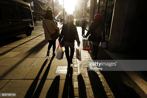 Shoppers carry multiple branded shopping bags on Regent Street in London UK on Friday Nov 25 2016 Black Friday first became a part of UK shopping...