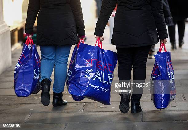 Shoppers carry Next Plc sales bags on Oxford Street during the Boxing Day sales in London UK on Monday Dec 26 2016 Consumer confidence fell to its...