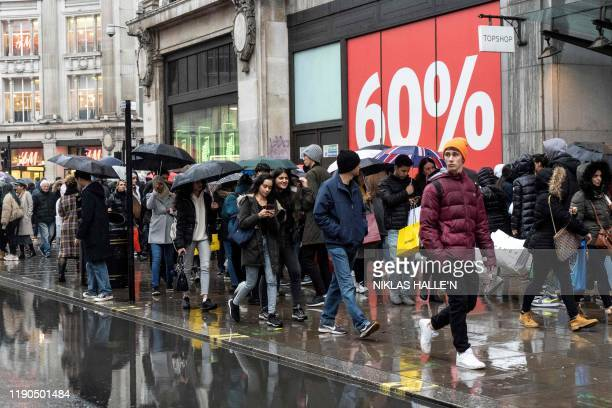 Shoppers carry packages as they hunt for bargains during the Boxing Day sales in central London on December 26 2019 With environmental concerns...