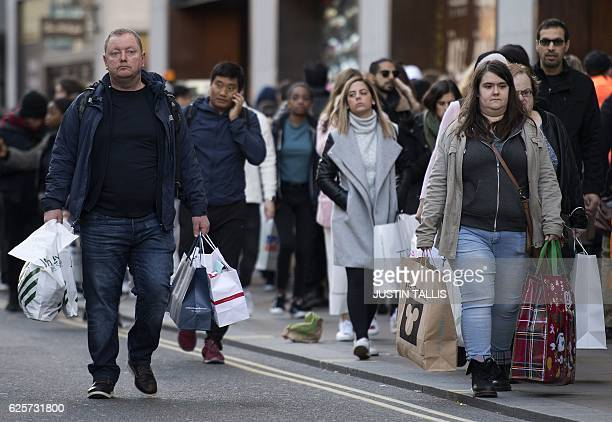 Shoppers carry plastic bags containing purchases from John Lewis Primark and Disney stores as they walk along Oxford Street on 'Black Friday' in...
