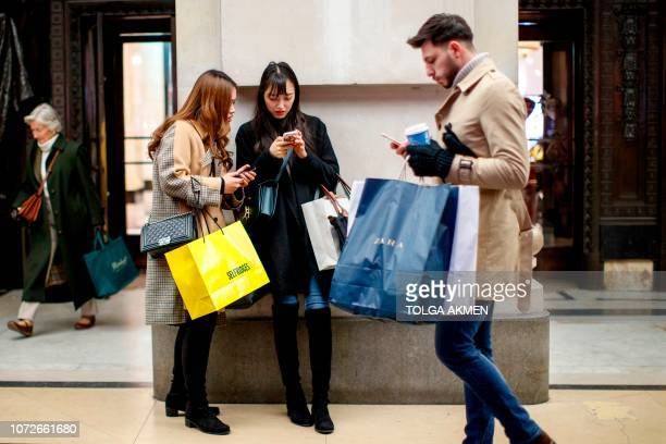 Shoppers carry purchases as they look at their smartphones on the main shopping district on Oxford Street in London on December 13 2018 less than two...