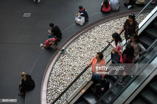 Shoppers carry retail bags while riding down an escalator at the Plaza Reforma 222 mall in Mexico City Mexico on Monday Nov 20 2017 The National...