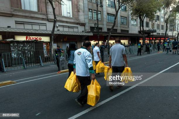 Shoppers carry retail bags while walking along a street in Mexico City Mexico on Monday Nov 20 2017 The National Institute of Statistics and...