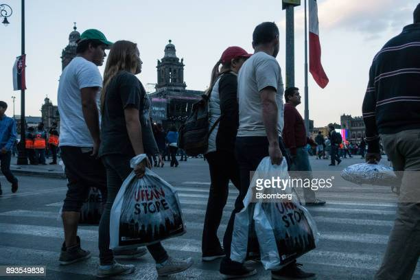 Shoppers carry retail bags while walking in front of the main square in Mexico City Mexico on Monday Nov 20 2017 The National Institute of Statistics...