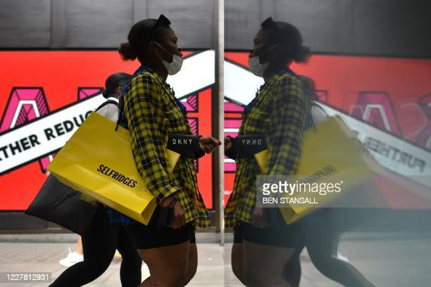 Shoppers carry Selfridges bags as they walk past Selfridges flagship store on Oxford street in central London on July 28, 2020. - British department...