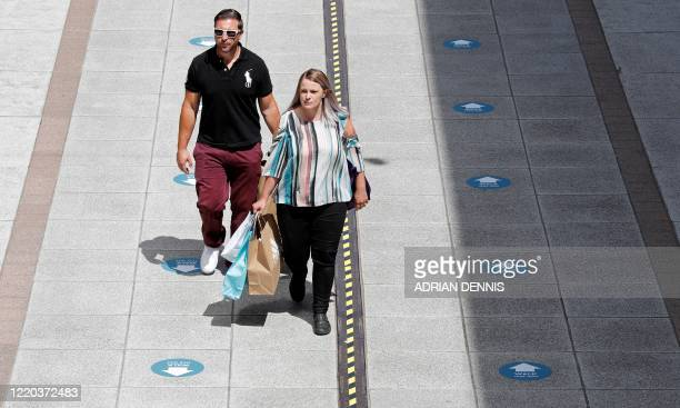 Shoppers carry shopping bags as they walk along a footpath laid out with social distancing measures including a oneway walking system at Gunwharf...