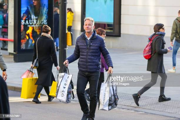 Shoppers carry shopping bags on Oxford Street during the Black Friday event Black Friday is a shopping event where retailers cut prices on the day...