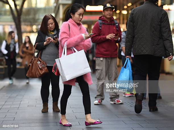 Shoppers carry their bags while walking through the central business district in Sydney on September 3 2014 Australia's economy lost pace in the...