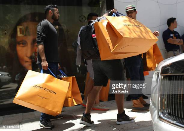 Shoppers carry their Louis Vuitton bags from the store where they were selling limited edition supreme and Louis Vuitton collaboration items on June...