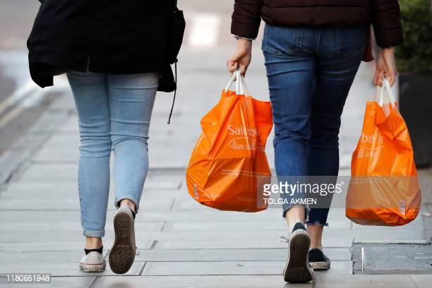 Shoppers carry their purchases in orange plastic Sainsbury's supermarket store shopping bags as they walk in London on November 7 2019 Sainsbury's...