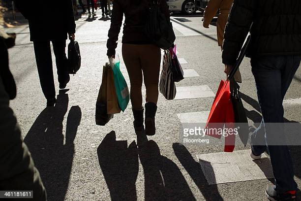 Shoppers carry their purchases in shopping bags on the first day of sales in Madrid Spain on Tuesday Jan 7 2014 In Spain which has the euro area's...
