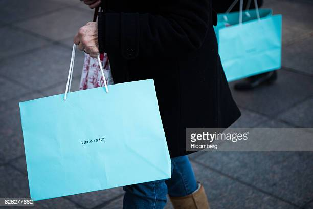 Shoppers carry Tiffany Co bags while walking on Fifth Avenue in New York US on Saturday Nov 26 2016 Tiffany Co is scheduled to release earnings...