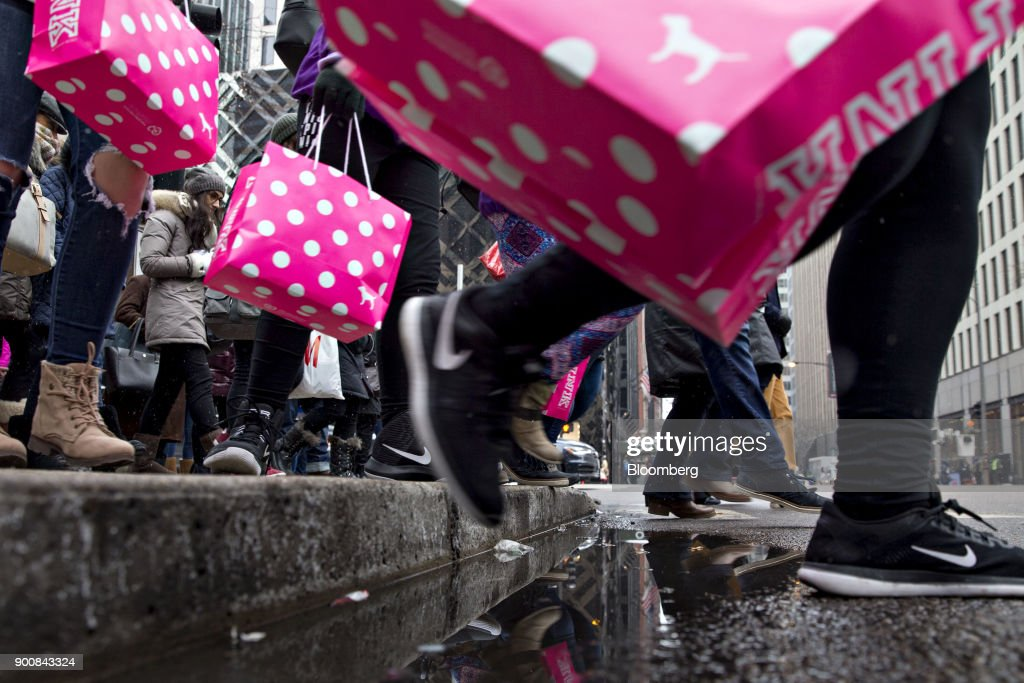 Shoppers carry Victoria's Secret Stores LLC Pink bags while walking through the Magnificent Mile commercial district in Chicago, Illinois, U.S., on Friday, Dec. 29, 2017. Bloomberg is scheduled to release consumer comfort figures on January 4. Photographer: Daniel Acker/Bloomberg via Getty Images