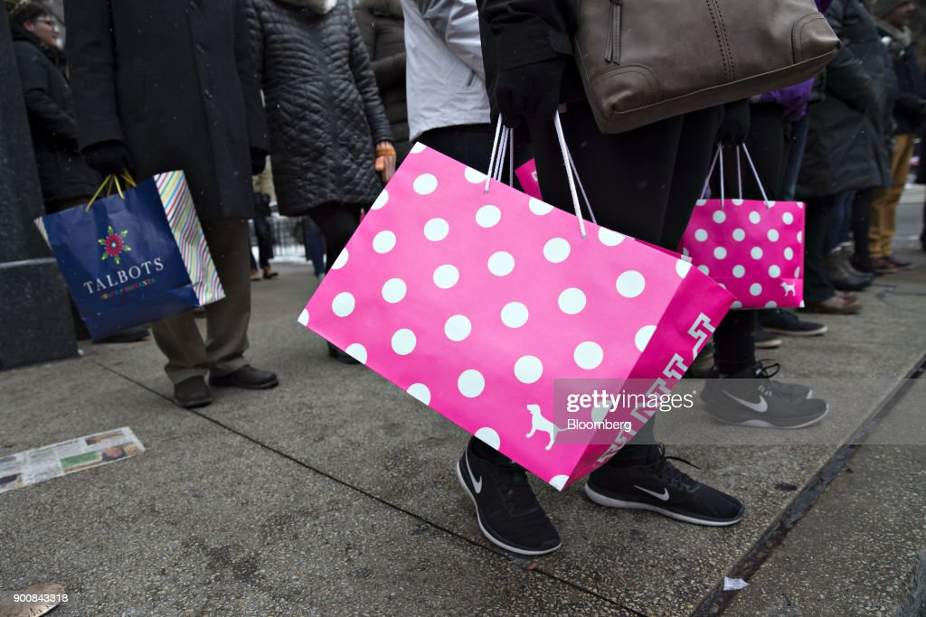 Shoppers carry Victoria's Secret Stores LLC Pink brand and Talbots Inc. bags while walking through the Magnificent Mile commercial district in Chicago, Illinois, U.S., on Friday, Dec. 29, 2017. Bloomberg is scheduled to release consumer comfort figures on January 4. Photographer: Daniel Acker/Bloomberg via Getty Images
