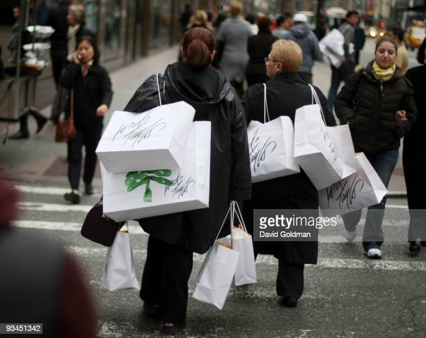 Shoppers carrying bags walk up Fifth Avenueon Black Friday November 27 2009 in New York City Black Friday is the traditional kickoff to the holiday...