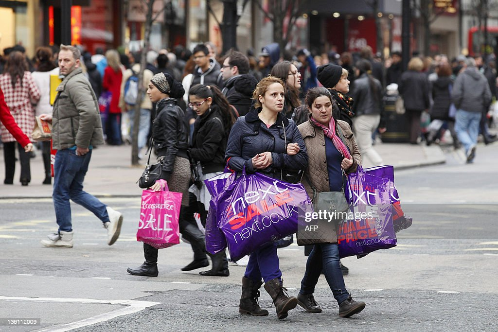 Shoppers carrying large sale bags walk a : News Photo