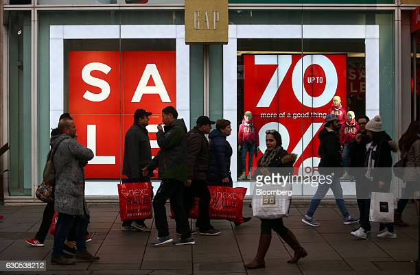 Shoppers carrying sales bags pass a Gap Inc fashion retail store on Oxford Street during the Boxing Day sales in London UK on Monday Dec 26 2016...