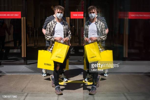 Shoppers carrying the iconic yellow Selfridges shopping bag are reflected in a bus shelter as they leave the department store on July 28, 2020 in...