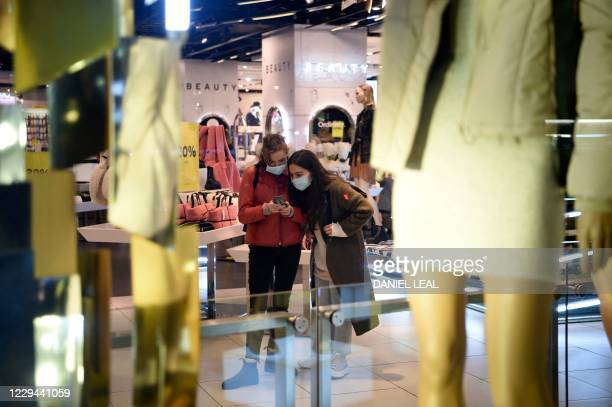 Shoppers check their mobile phone as they browse in a Topshop store on Oxford Street in central London on November 3 as the country prepares for a...