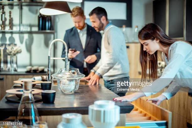 käufer, die neue funktionen und accessoires in einer designer-küchenanzeige eines küchenverbesserungsgeschäfts auschecken - küchenbedarf stock-fotos und bilder