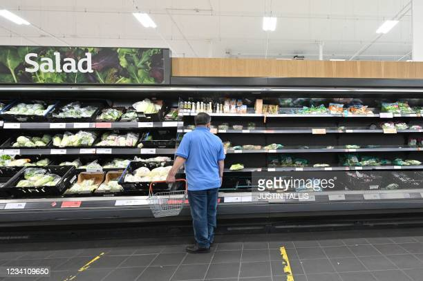 Shoppers choose products from partially filled shelves in a supermarket at Nine Elms, south London on July 22, 2021. - British supermarkets and...