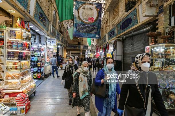 Shoppers clad in protective gear, including face masks and latex gloves, due to the COVID-19 coronavirus pandemic, walk through the Tajrish Bazaar in...