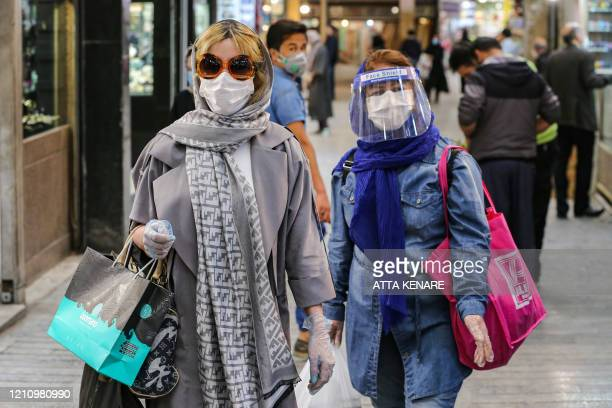 Shoppers clad in protective gear, including face masks and shields and latex gloves, due to the COVID-19 coronavirus pandemic, walk through the...