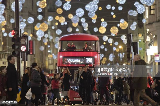Shoppers cross in front of a London bus as it travels under Christmas lights on Oxford Street in central London on December 5 2017 / AFP PHOTO /...