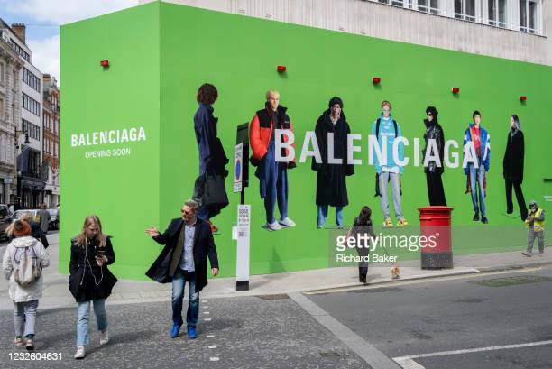 Shoppers cross the road towards the temporary hoarding for Balenciaga, a retail space which is opening soon on Bond Street, on 27th April 2021, in...
