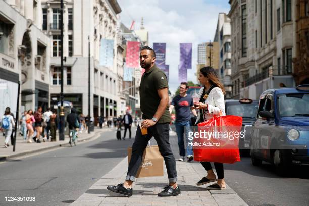 Shoppers cross the street at Oxford Circus on July 31, 2021 in London, England. The United Kingdom, considered one of the advanced world's worst hit...