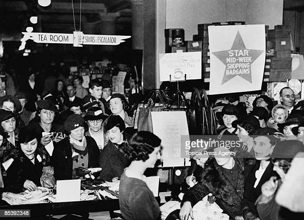 Shoppers crowd round a counter at Selfridges department store on Oxford Street, London, 7th December 1939.
