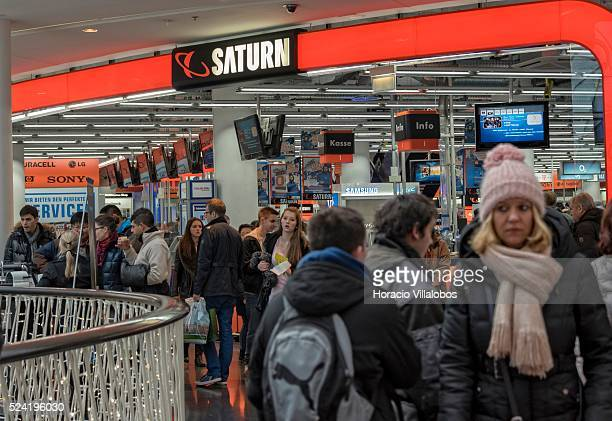 Shoppers crowd the entrance to Saturn one of the big players in German electronics retail business at Christmas decorated MyZeil Shopping Center in...
