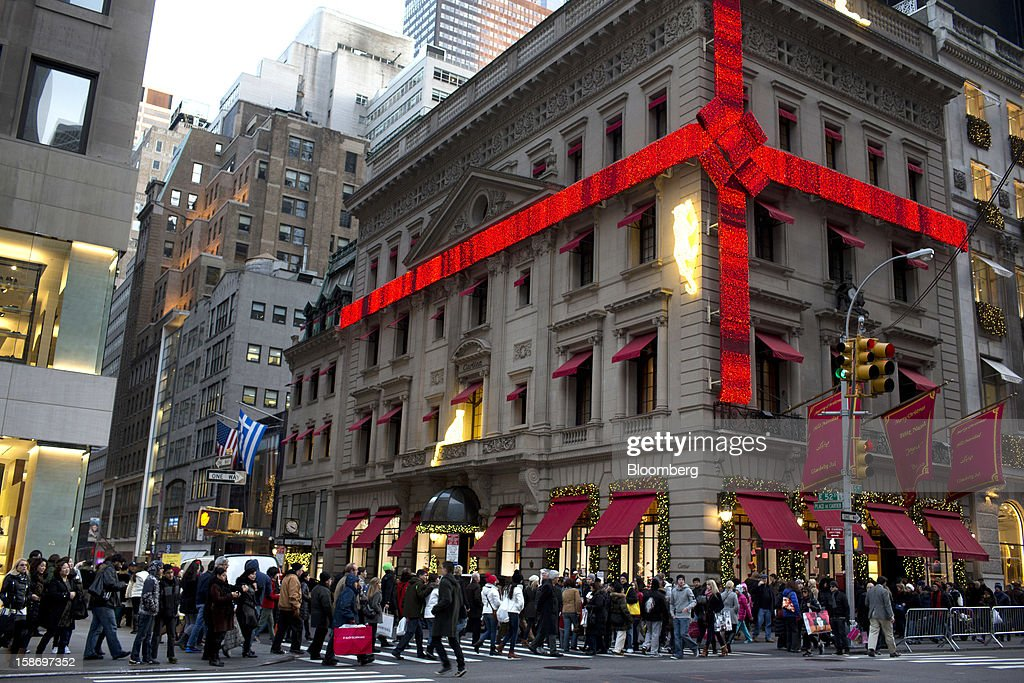 Shoppers crowd the sidewalk around the Cartier Mansion wrapped in a red bow for the holidays, on Fifth Avenue in New York, U.S., on Sunday, Dec. 23, 2012. Holiday shoppers descended on U.S. stores this weekend in a last-minute dash to buy gifts amid concerns about the nation's economy and the impasse in Washington over taxes and spending. Photographer: Victor J. Blue/Bloomberg via Getty Images
