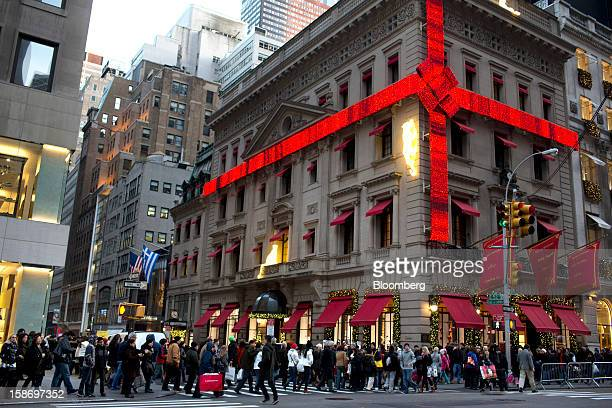 Shoppers crowd the sidewalk around the Cartier Mansion wrapped in a red bow for the holidays on Fifth Avenue in New York US on Sunday Dec 23 2012...