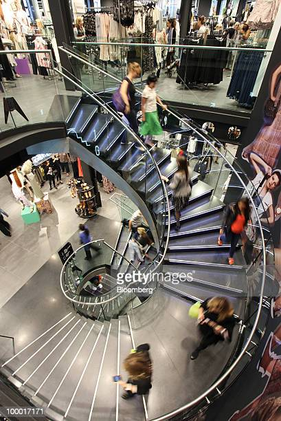 Shoppers descend stairs at a Topshop retail store in London UK on Thursday May 20 2010 Sir Philip Green the billionaire owner of Arcadia Group Ltd...
