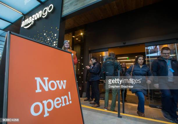 Shoppers enter and exit the Amazon Go store on January 22 2018 in Seattle Washington After more than a year in beta Amazon opened the cashierless...