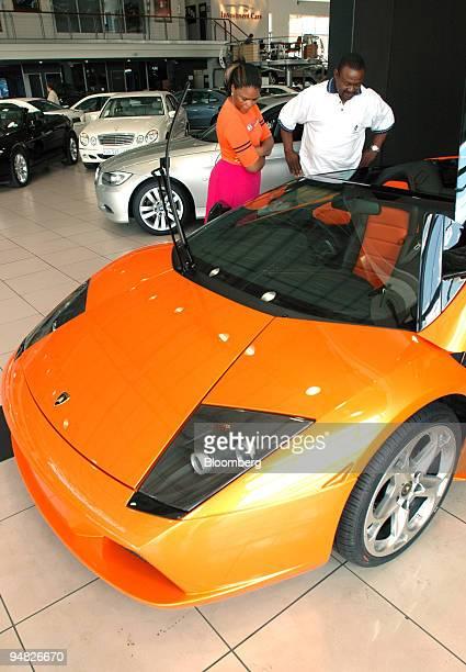Shoppers examine a Lamborghini sports car in Sandton Johannesburg South Africa Tuesday December 21 2005