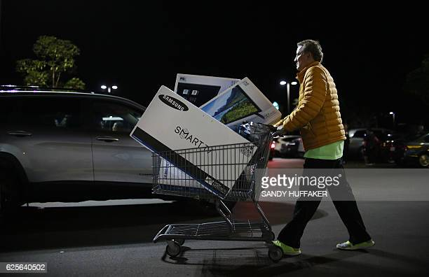 Shoppers exit a Best Buy after purchasing electronic items during Black Friday sales in San Diego California on November 24 2016 / AFP / Sandy...
