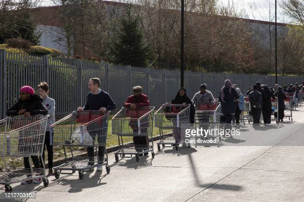 Shoppers form long queues ahead of the opening of a Costco wholesale store in Chingford on March 16 2020 in London England Coronavirus has spread to...