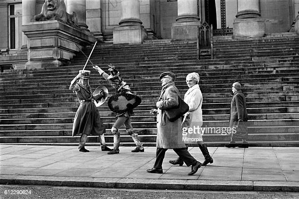 Shoppers hurry past the Town Hall steps as a couple of medieval knights are locked in combat in Bolton The battle was being filmed by the Bolton...