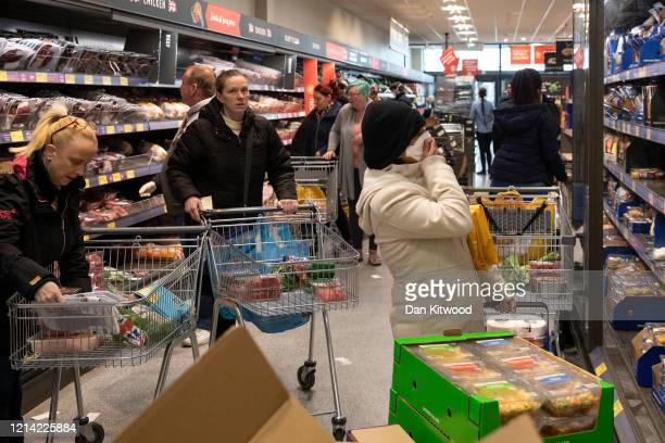 Shoppers in an Aldi supermarket ahead of opening on March 23 2020 in London England Coronavirus pandemic has spread to at least 182 countries...