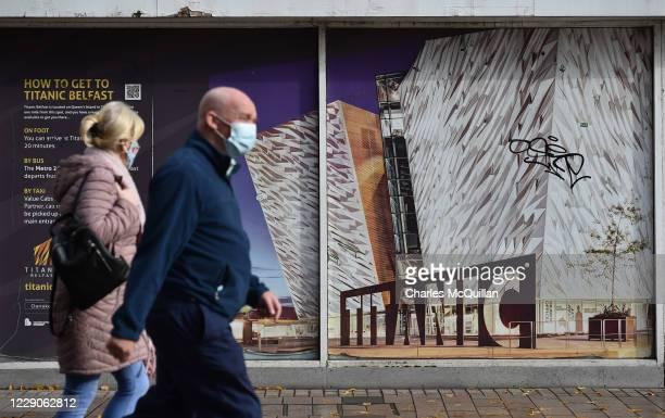 Shoppers in Belfast city centre wearing face masks walk past a Titanic Belfast billboard on October 14, 2020 in Belfast, Northern Ireland. The...