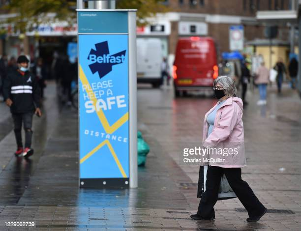 Shoppers in Belfast city centre wearing face masks walk past a public health advice billboard on October 14, 2020 in Belfast, Northern Ireland. The...