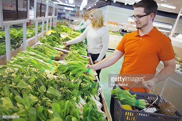 Shoppers in grocery store selecting vegetables