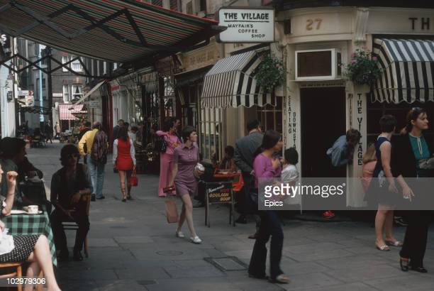 Shoppers in London's Shephard Market walk past 'The Village Coffee Shop' Mayfair August 1970