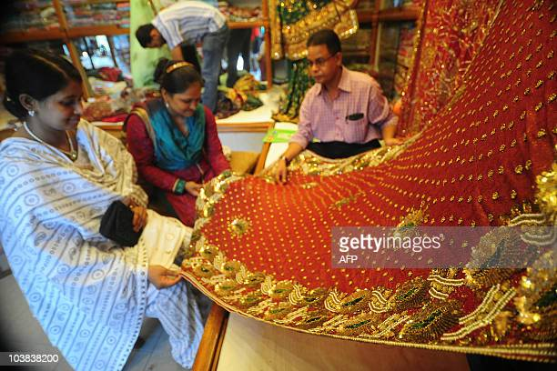 Shoppers inspect saris at a textile shop during the Islamic holy month of Ramadan in Dhaka on August 30 2010 Ramadan is the Muslim majority nation�s...